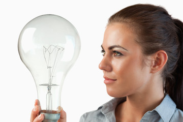 Businesswoman looking at huge light bulb in her hand