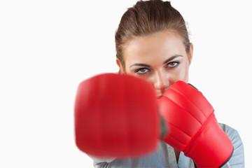 Close up of businesswoman striking with boxing gloves