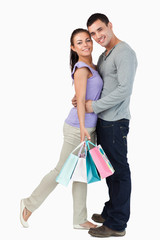 Young male hugging his girlfriend during shopping tour