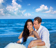 couple in love sitting in blue beach