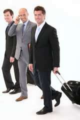 Three businessmen walking with luggage bag