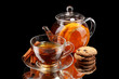 Glass teapot and cup with black fruit tea and cookies