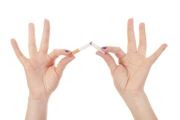 Woman's hand crushing cigarette on white background