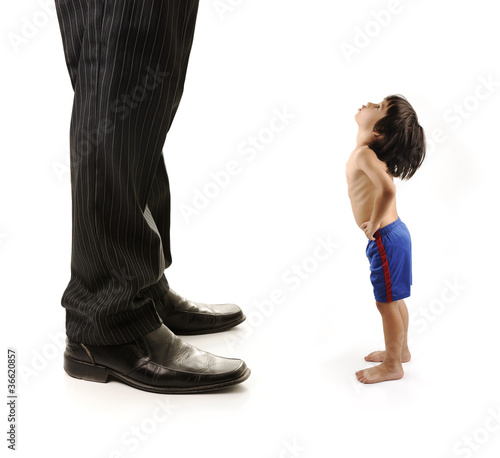 Little small child  is looking at the giant legs of  businessman