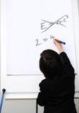 Genius little boy writting E=mc2 on the board poster