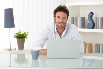 Portrait of man at home with computer