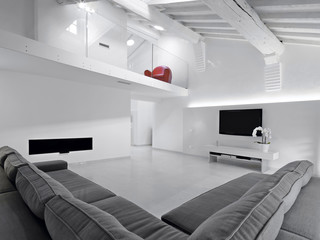 soggiorno con divano grigio in mansarda