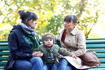 Two female friends with young boy sitting on bench in city park