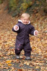 Kleines Mädchen spielt im herbstlichen Park