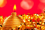 Christmas card of golden bauble candle on tinsel