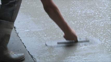 рабочий выравнивает цементный пол