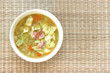 Vegetable cabbage soup in white bowl with bacon pieces