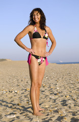 A happy forties woman on beach wearing bikini