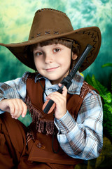 Portrait of a cute boy in a cowboy suit with a pistol on a green