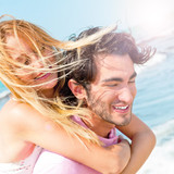 An attractive couple fooling around on the beach poster