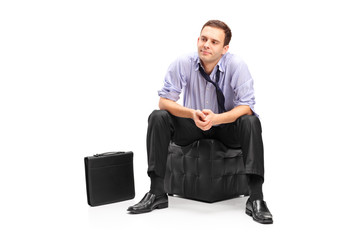A studio shot of a disappointed businessman sitting