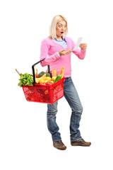 Surprised woman looking at store receipt and holding a shopping