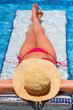 Woman in hat tanning on holiday at swimming pool bed poster