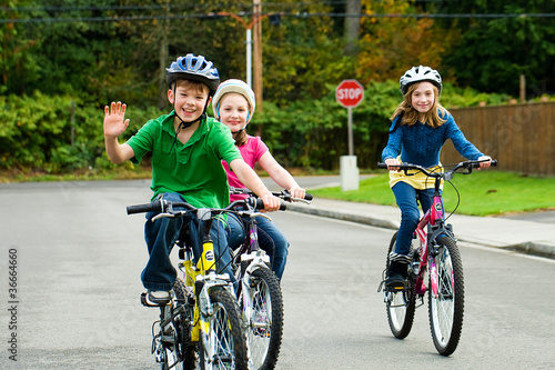 Kids riding bicycles in the street - 36664660