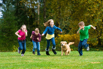 Group of kids racing a dog