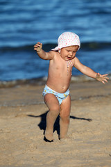 Cute toddler girl playing on the beach