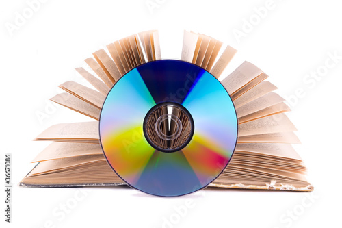 Compact disc on an open book isolated on white
