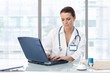 Female doctor sitting at table with laptop
