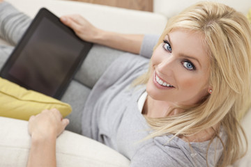 Beautiful  Women Using Tablet Computer At Home on Sofa