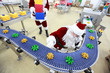 santa claus at christmas ornament production line in factory