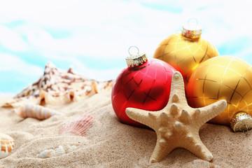 Christmas balls and seashells on the beach