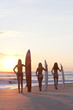 Women Surfers In Bikinis With Surfboards At Sunset Beach