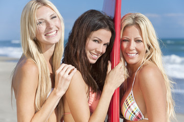 Three Beautiful Women Surfers In Bikinis With Surfboard At Beach