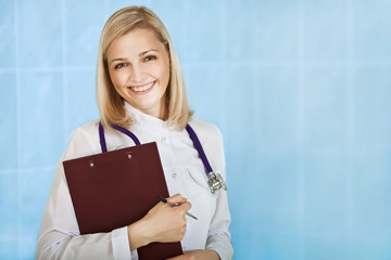 Smiling young female medical doctor with stethoscope and clipboa
