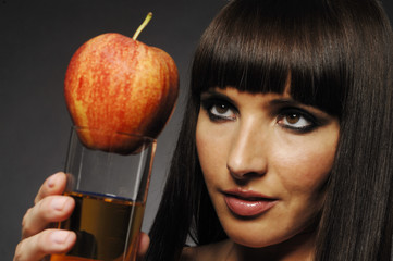 Hübsche Frau mit Apfel und Apfelsaft in der Hand