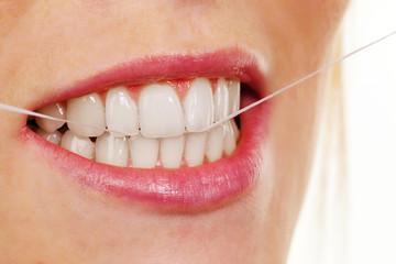 Frau verwendet Zahnseide