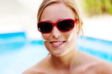 Frau mit Sonnenbrille und Sonnen Creme