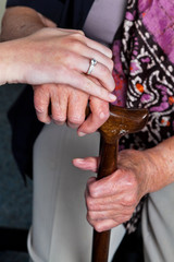 Alte und junge Hand mit Gehstock