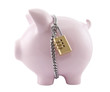 Piggy bank secured with padlock. Clipping path included