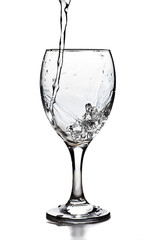 Water pouring into the glass over white background