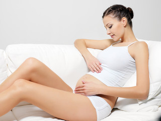 Happy pregnant woman sitting on sofa