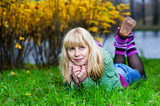Blond woman in gaiters lying on the grass