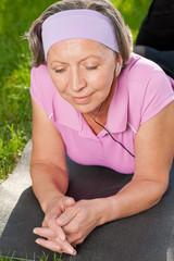 Senior sportive woman listen music on mat