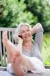 attraktive, grauhaarige Frau telefoniert im sommerlichen Garten