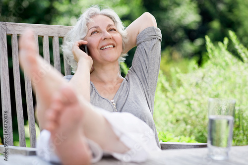 Leinwanddruck Bild attraktive, grauhaarige Frau telefoniert im sommerlichenGarten