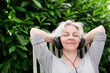 attraktive, grauhaarige Frau mit Kopfhörern im Garten