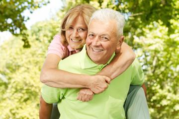 happy senior man giving piggyback ride