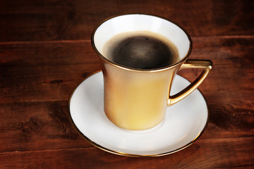 golden cup of coffee on wooden table