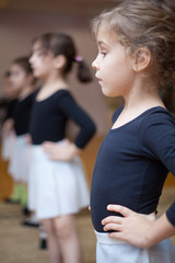 Young ballerinas stand in first position.