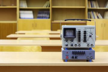 Old educational oscilloscope on desk in physics school class