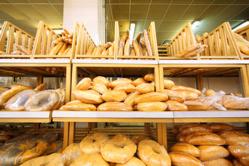 lots of fresh crisp loaves of bread on shelves in store